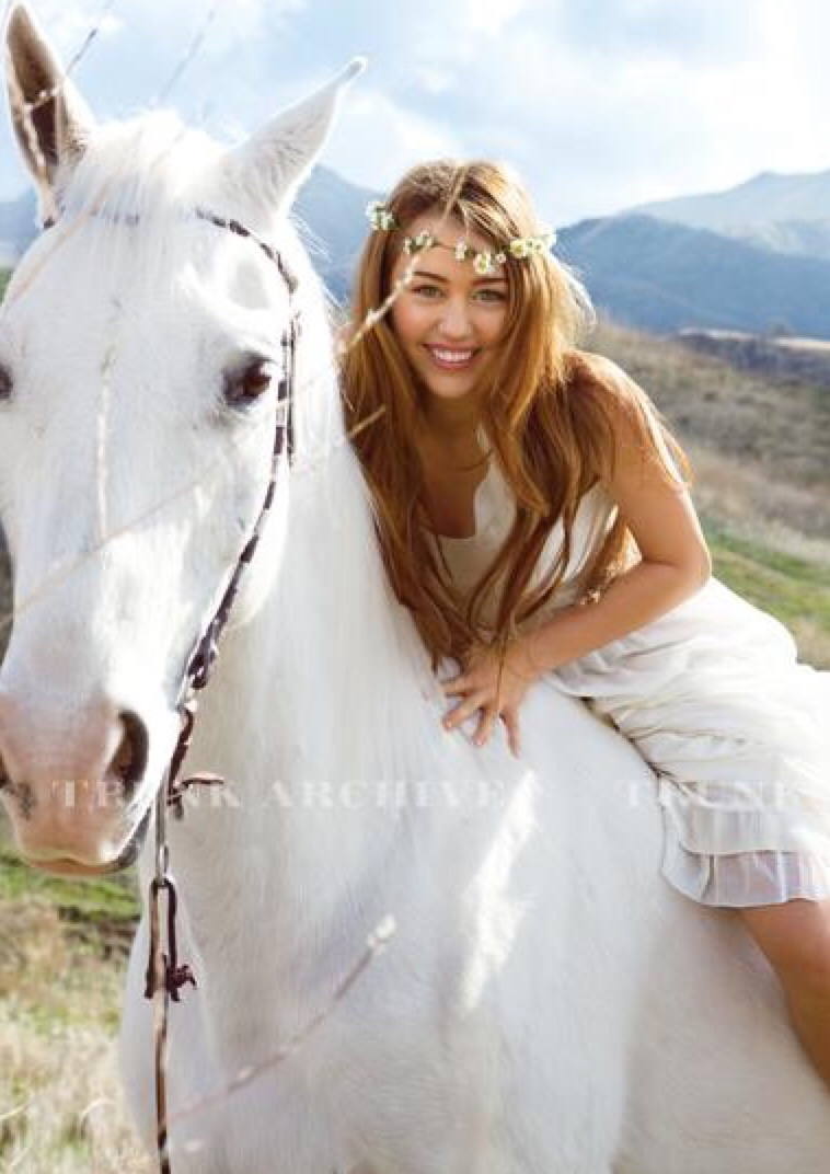 Miley Cyrus riding a horse